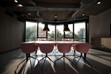 Office with large glass windows and pink swivel chairs designed by fit-out contractors Glasgow