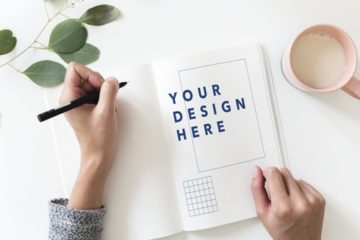 Birds eye view of desk with person designing logo on notebook